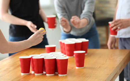Woman with friends playing beer pong in bar