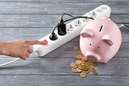 Piggy bank, coins and power strip on table. Electricity saving concept Stock Photo