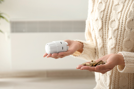 Woman holding thermostat and coins at home. Heating saving concept