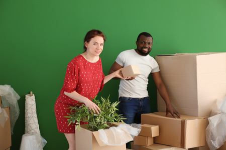 Interracial couple unpacking boxes indoors. Moving into new house Stock Photo - 114429346