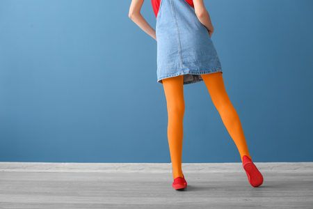 Stylish woman in bright tights against color wall 免版税图像