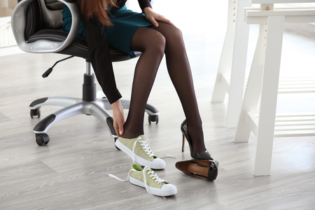 Tired businesswoman changing shoes at workplace in office Фото со стока