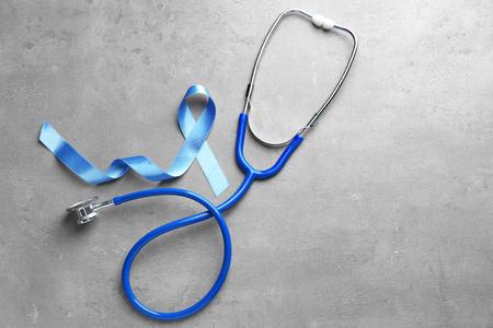 Blue ribbon and stethoscope on grey background. Prostate cancer awareness