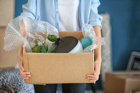Woman with packed carton box indoors. Moving house concept Stock Photo