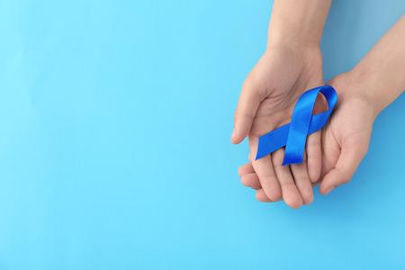 Male hands holding blue ribbon on color background. Prostate cancer concept