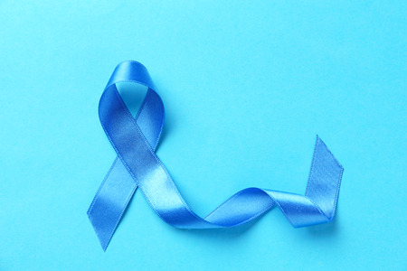 Blue ribbon on color background. Prostate cancer concept