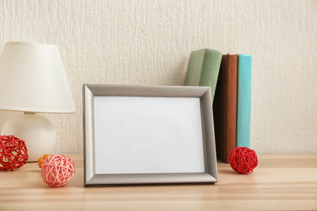 Composition with photo frame on table against light background