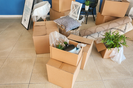 Carton boxes and interior items on floor in room. Moving house concept 版權商用圖片