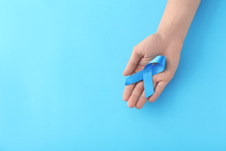 Male hand holding blue ribbon on color background. Prostate cancer concept