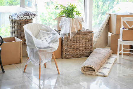 Cajas de cartón y artículos de interior en el piso de la habitación. Concepto de casa móvil