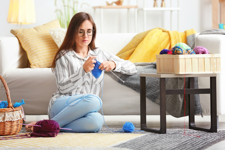 Young woman sitting on carpet and knitting warm sweater at home