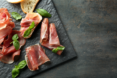Slate board with tasty prosciutto slices and basil on table