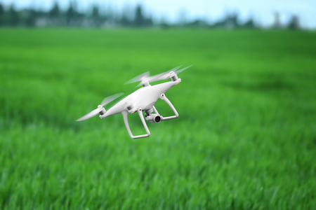 Modern quadcopter flying over field Archivio Fotografico