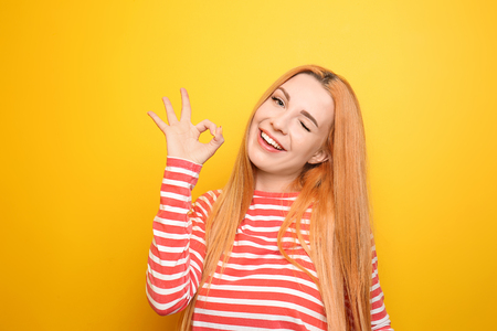 Beautiful young woman showing OK gesture on color background