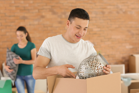 Young man unpacking boxes indoors. Moving into new house