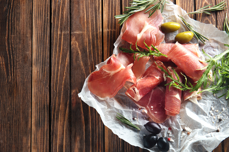 Tasty prosciutto slices with olives and herbs on wooden table