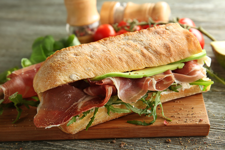 Tasty sandwich with prosciutto on wooden board, closeup 免版税图像