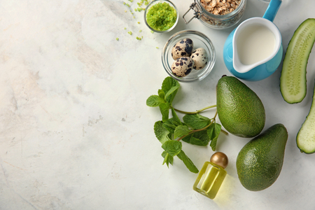 Avocado with ingredients for natural homemade cosmetics on light background
