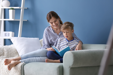 Mother and her son reading book together at home