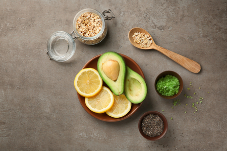 Avocado with ingredients for natural homemade cosmetics on grey background