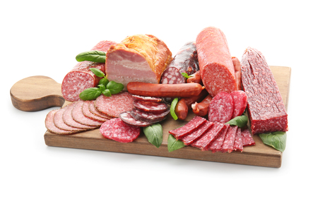 Assortment of delicious deli meats on wooden board, isolated on white Фото со стока