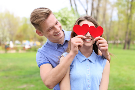 Happy young couple with paper hearts in park on spring day Imagens