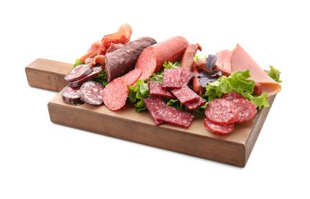 Surtido de deliciosas carnes frías en tablero de madera, aislado en blanco