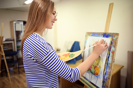 Young female artist painting still life in workshop