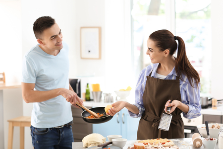 Young couple cooking together in kitchen Standard-Bild
