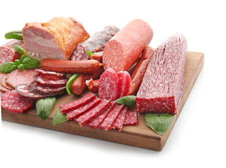 Assortment of delicious deli meats on wooden board, isolated on white Zdjęcie Seryjne