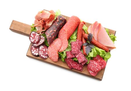 Assortment of delicious deli meats on wooden board, isolated on white Stock Photo