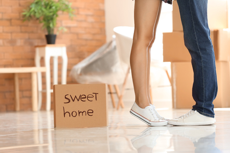 Piece of cardboard with text SWEET HOME and young couple indoors
