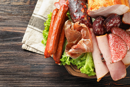 Assortment of delicious deli meats on wooden board Stock Photo