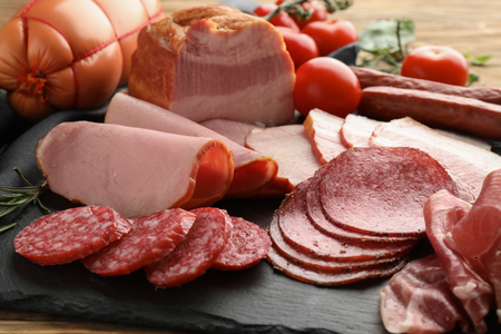 Assortment of delicious deli meats on slate plate Archivio Fotografico