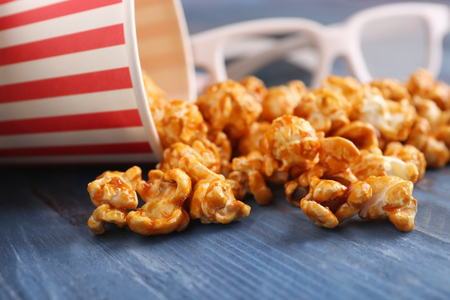 Overturned cup with scattered caramel popcorn on table, closeup Imagens
