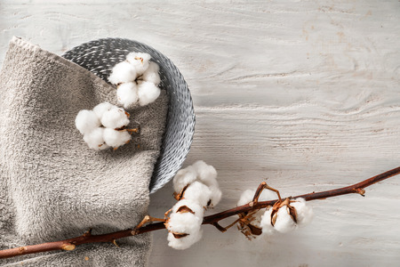 Basket with towel and cotton flowers on wooden background Фото со стока