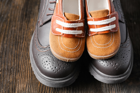 Big and small shoes on wooden background. Fathers day celebration Stockfoto