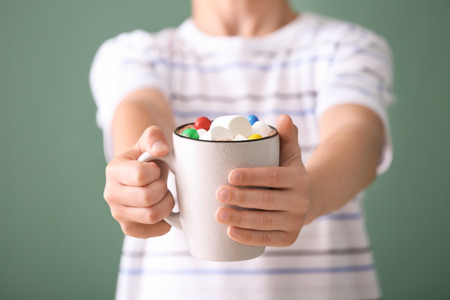 Cute little boy with cup of hot cocoa drink on color background, closeup