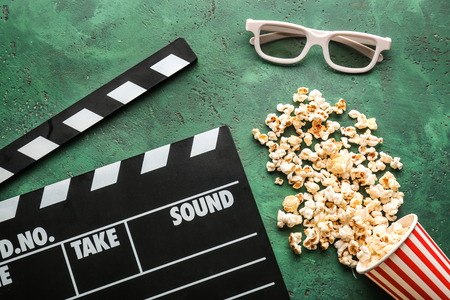 Composition with tasty popcorn and clapperboard on green background Stockfoto