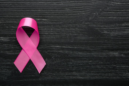 Pink ribbon on wooden background. Breast cancer concept