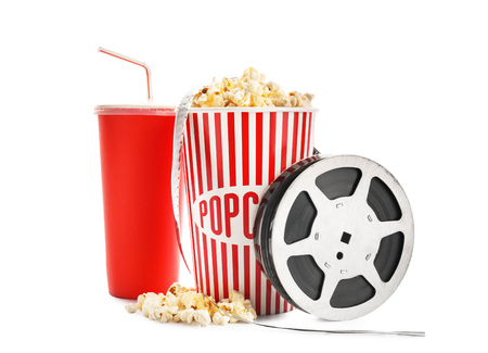 Cup with tasty popcorn, beverage and film reel on white background