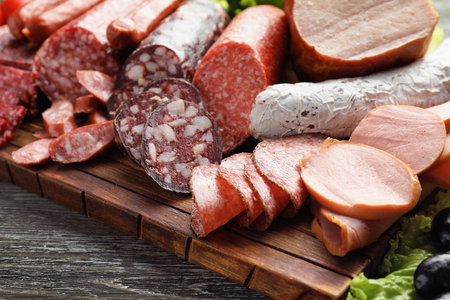 Assortment of delicious deli meats on wooden board