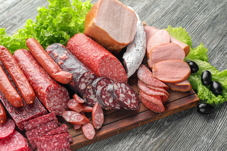 Assortment of delicious deli meats on wooden board Stockfoto