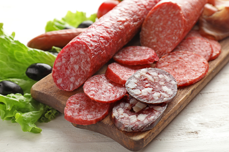 Wooden board with assortment of delicious sausages on light table