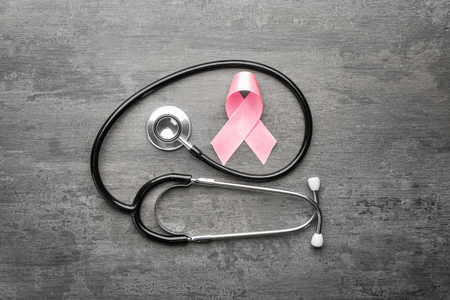 Pink ribbon and stethoscope on grey background. Breast cancer awareness concept