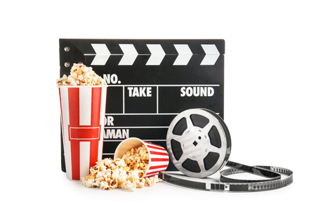 Cups with tasty popcorn, film reel and clapperboard on white background
