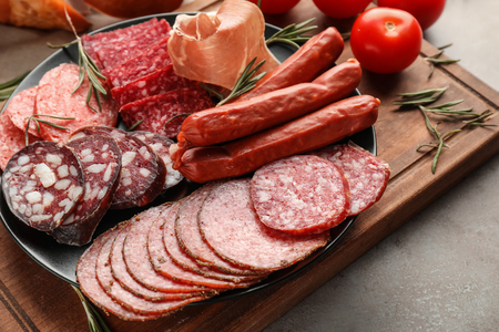 Plate with assortment of delicious deli meats on wooden board Stock Photo