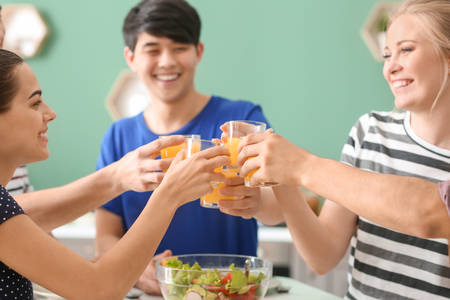 Young friends clinking glasses with juice in kitchen