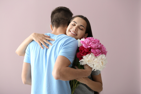 Happy young woman with flowers embracing her boyfriend on color background