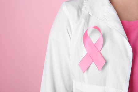 Doctor with pink ribbon on robe against color background, closeup. Breast cancer awareness concept